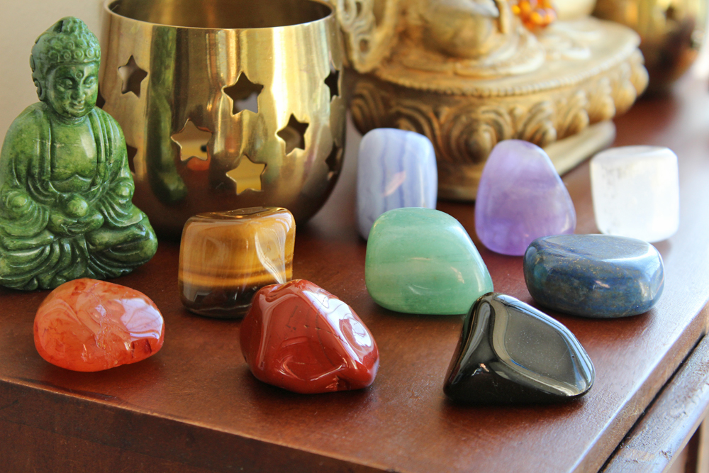 nine chakra crystal set on an altar with buddhas and candles