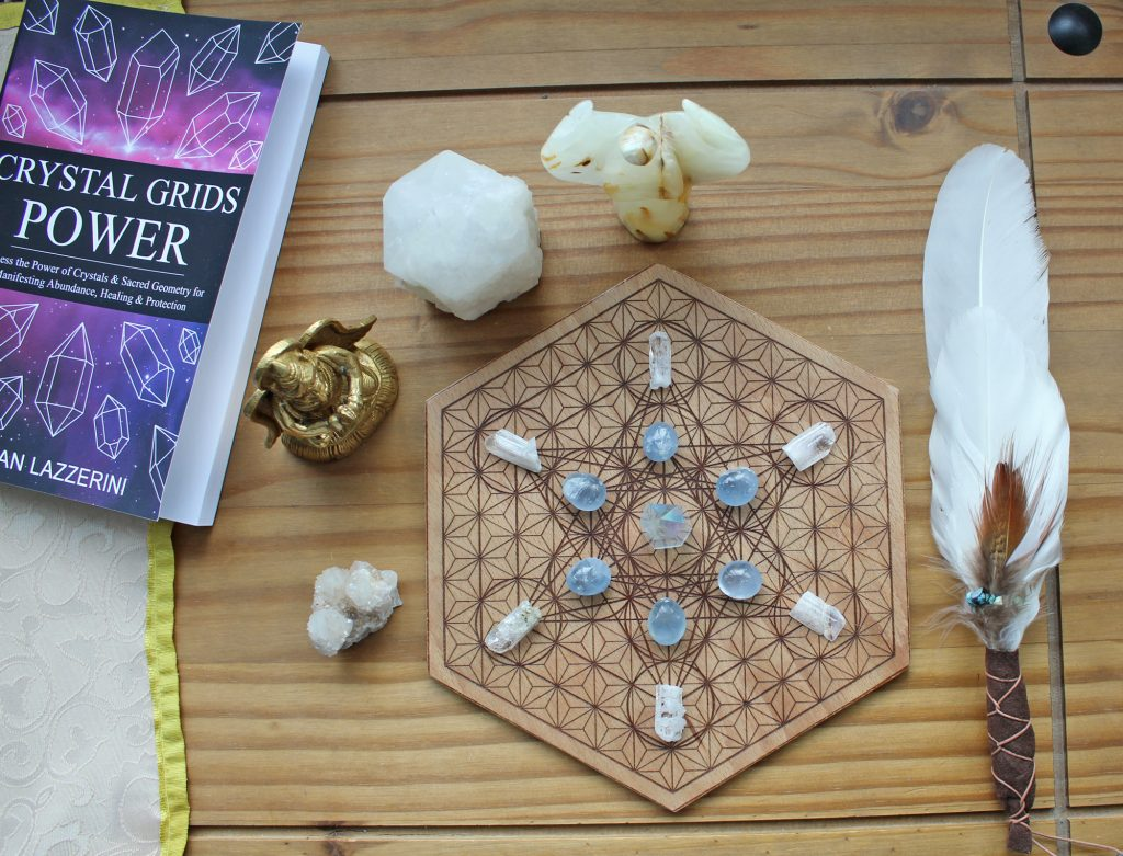 Metatrons cube crystal grid and crystal grids power book. Smudge feather, crystals and brass statue