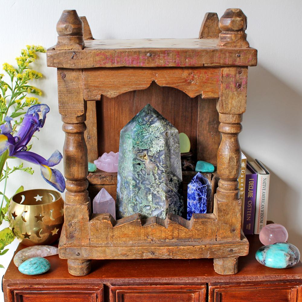 Mini altar with crystals, books, candle and flowers